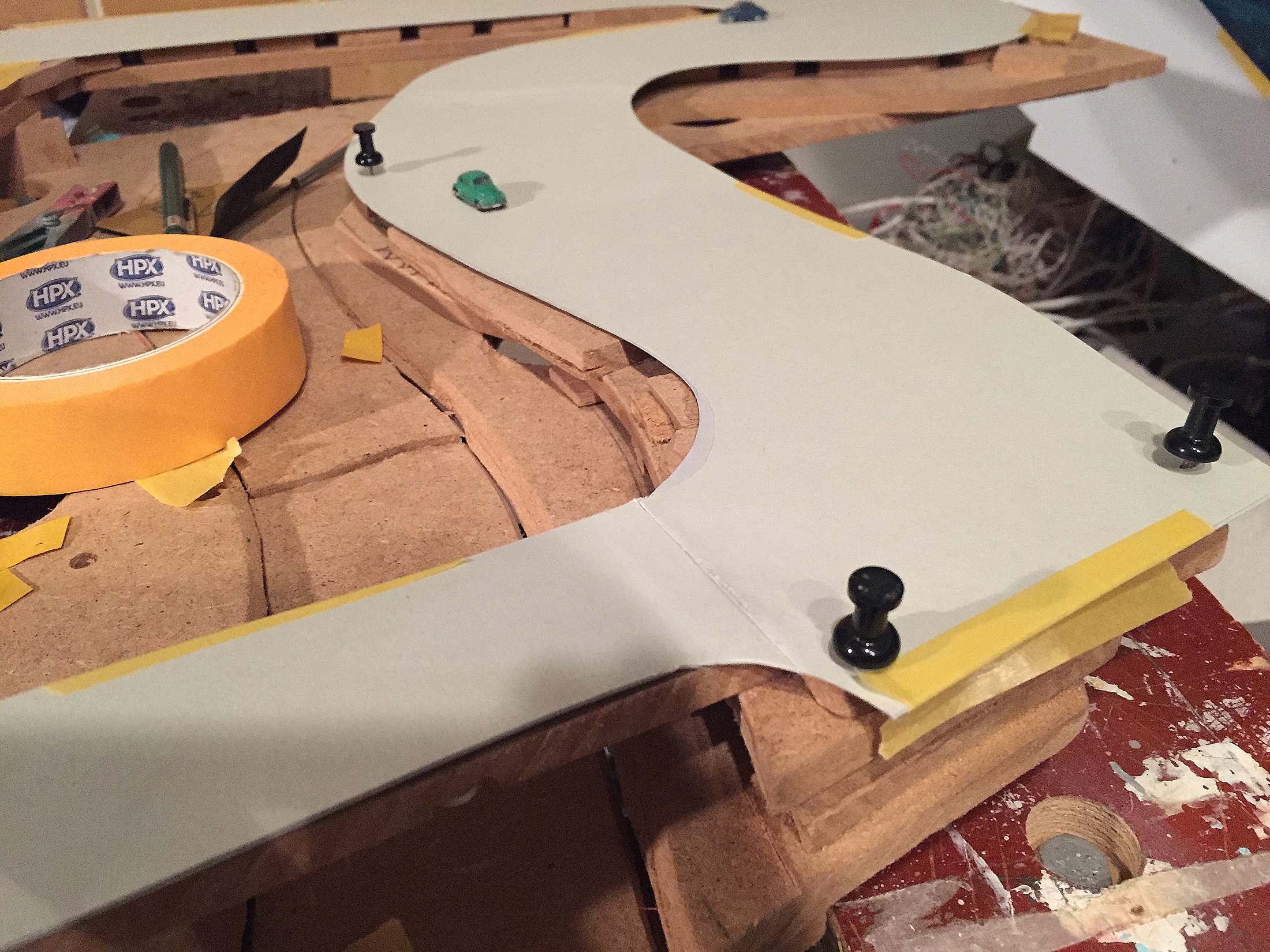 Dan is het tijd voor proefritjes. De kartonlaag die als wegdek dient is even provisorisch vastgezet.